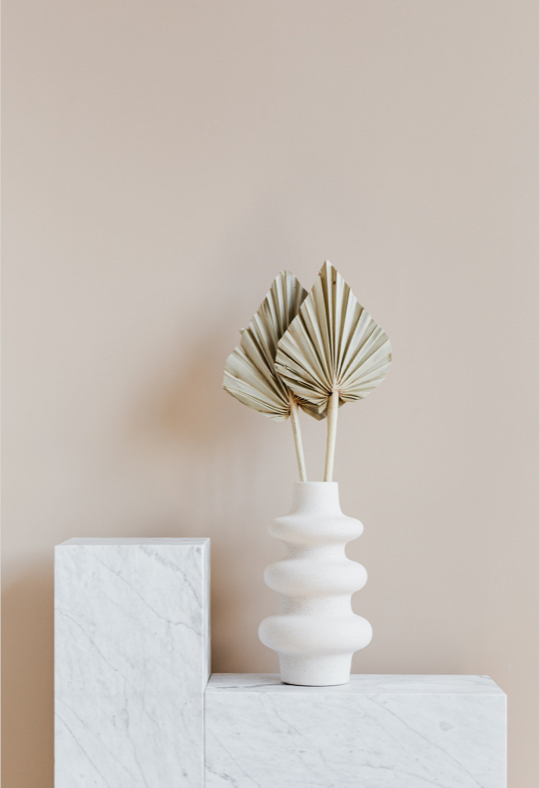 Vase blanc posé sur un meuble design