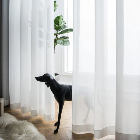 Statuette de chien qui se cache derrière un rideau blanc
